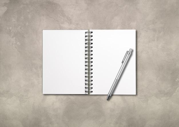 Maquete de caderno espiral aberto em branco e caneta isoladas no fundo de concreto