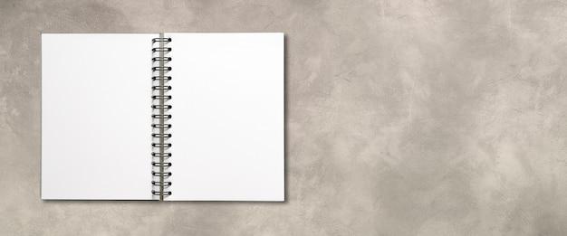 Maquete de caderno espiral aberto em branco isolada em banner de concreto