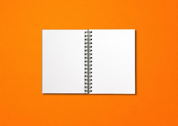 Maquete de caderno espiral aberto em branco isolada em fundo laranja