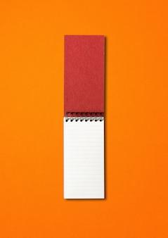 Maquete de caderno espiral aberto em branco isolada em laranja