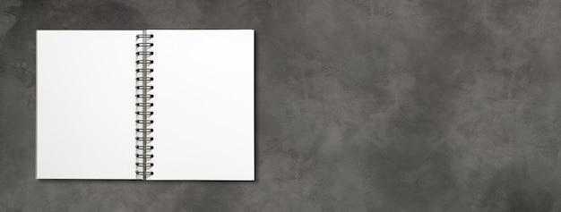 Maquete de caderno espiral aberto em branco isolada em um banner de concreto escuro