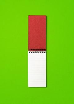 Maquete de caderno espiral aberto em branco isolada em verde