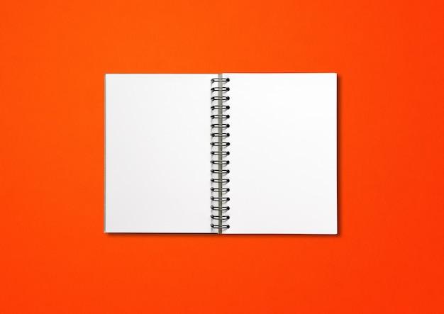 Maquete de caderno espiral aberto em branco isolada em vermelho