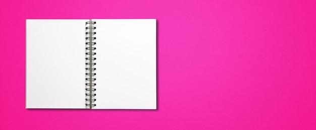 Maquete de caderno espiral aberto em branco isolada na superfície horizontal rosa