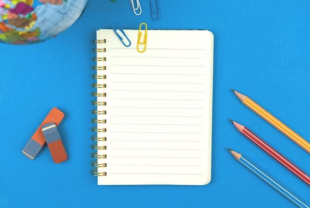 Maquete de caderno forrado em branco com papelaria escolar, lápis em fundo azul, foto de vista superior de composição plana