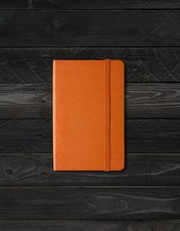 Maquete de caderno laranja fechado isolado em fundo preto de madeira