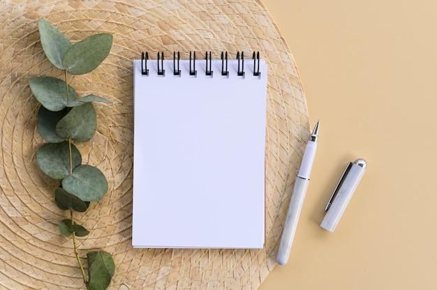 Maquete de caderno mínima. folha de papel em branco com espaço de cópia, caneta e folhas de eucalipto sobre prato de palha. vista do topo.