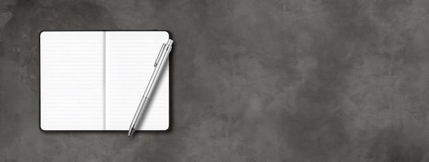 Maquete de caderno preto com forro aberto com uma caneta isolada em concreto escuro