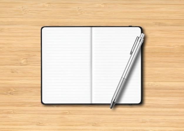 Maquete de caderno preto com forro aberto com uma caneta isolada em uma superfície de madeira