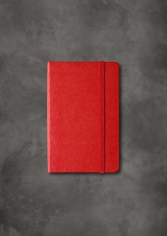 Maquete de caderno vermelho fechado isolado em concreto escuro