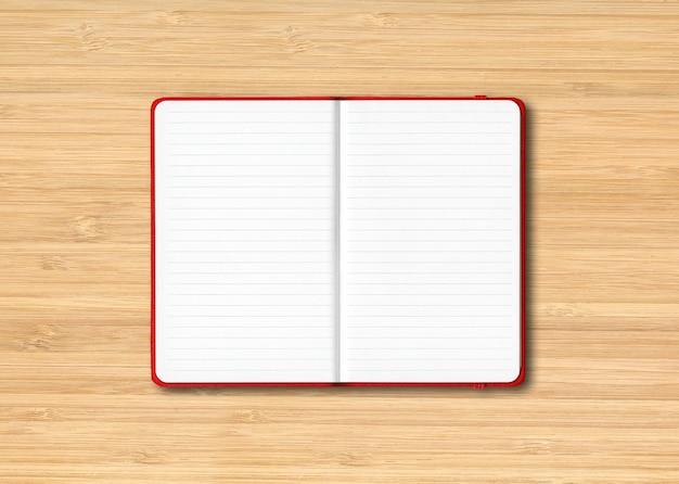 Maquete de caderno vermelho forrado aberto isolado em madeira