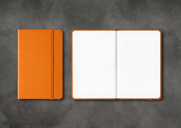 Maquete de cadernos forrados de laranja fechada e aberta isolada no fundo escuro de concreto