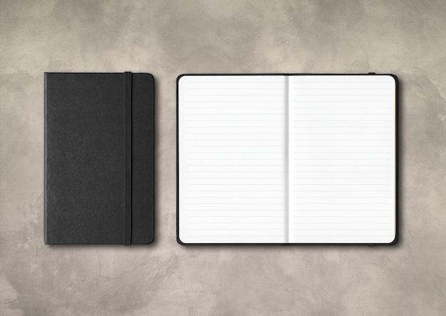 Maquete de cadernos pretos com forro fechado e aberto isolado no fundo de concreto