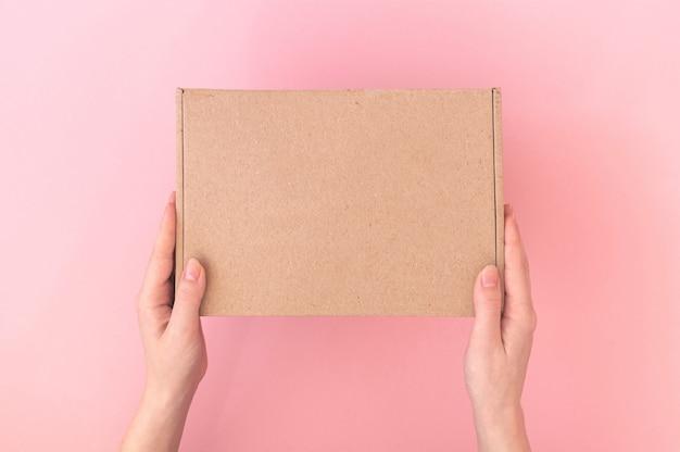 Maquete de caixa de papelão em um entregador com as mãos em um fundo rosa pastel, mesa, foto do conceito de serviço de entrega