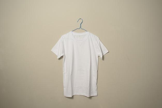 Maquete de camiseta branca em branco no cabide na vista lateral frontal do plano de fundo da parede