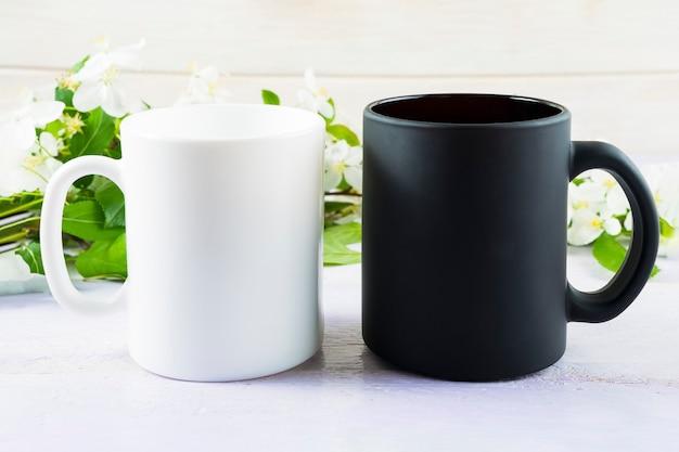 Maquete de caneca branca e preta com flor de maçã na primavera