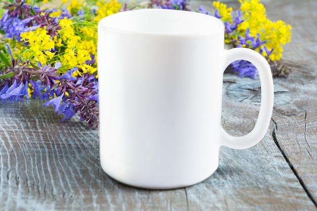 Maquete de caneca de café branco com flores lilás e amarelas