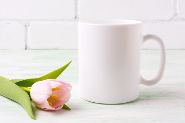 Maquete de caneca de café branco com tulipa rosa