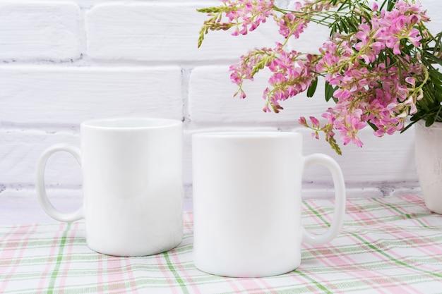 Maquete de caneca de café dois com pequenas flores cor de rosa