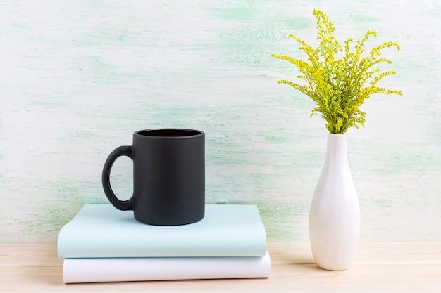 Maquete de caneca de café preta com grama verde ornamental