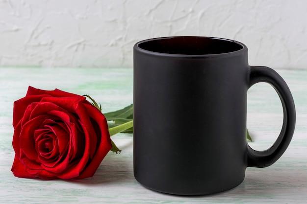 Maquete de caneca de café preta com linda rosa vermelha
