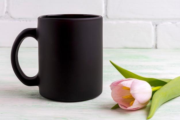 Maquete de caneca de café preta com tulipa rosa suave