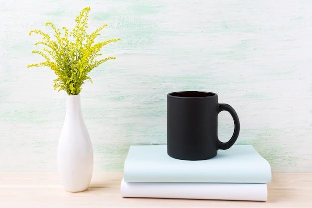Maquete de caneca de café preto com grama verde ornamental e livros