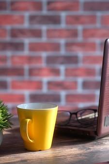 Maquete de caneca de cor amarela com laptop e bloco de notas na mesa