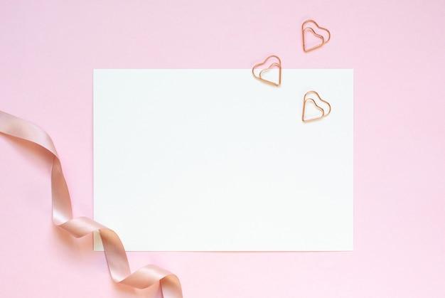Maquete de cartão a5 convite branco com três clipes de forma coração e fita de cetim em uma mesa rosa.