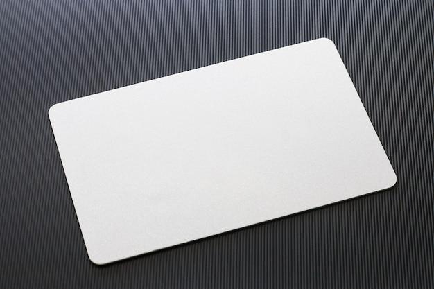Maquete de cartão branco em branco com cantos arredondados no plano de fundo texturizado preto.