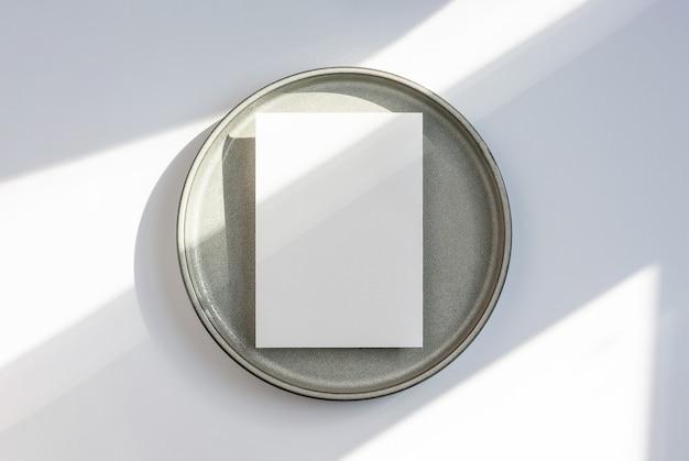 Maquete de cartão de convite ou negócios em branco em placa de cerâmica com sombras geométricas