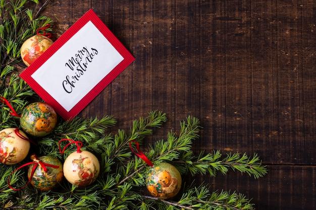 Maquete de cartão de natal com enfeites em fundo de madeira