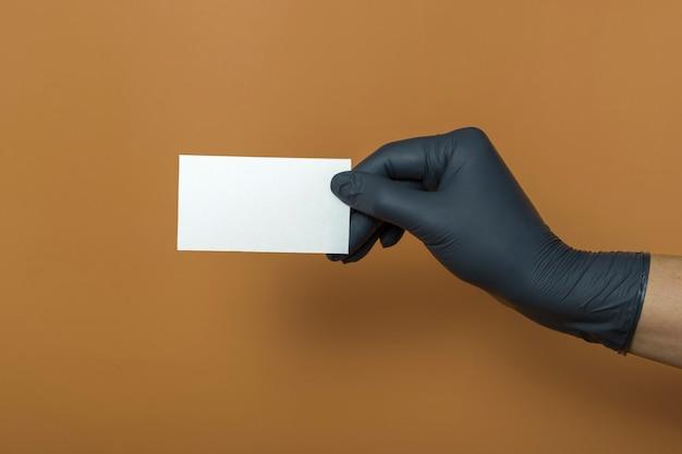 Maquete de cartão de visita branco sobre fundo colorido. uma mão em uma luva médica segura um cartão de visita