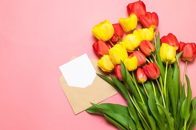Maquete de cartão minimalista com tulipas vermelhas, flor, envelope ofício