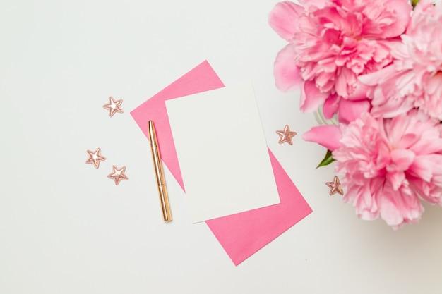 Maquete de cartão minimalista horizontal com flor, envelope ofício, flor, leigo plano, vista superior