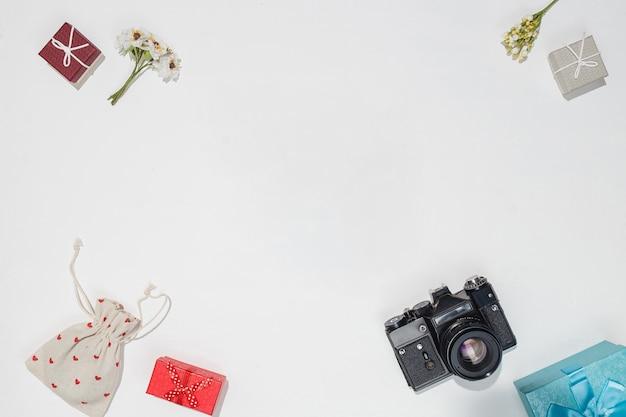 Maquete de cartão presente de primavera para fotógrafos. composição plana leiga com câmera retro, caixas de presente vermelhas, cinza e azuis, saco de lona com formas de coração vermelho e flores do campo de primavera em fundo branco