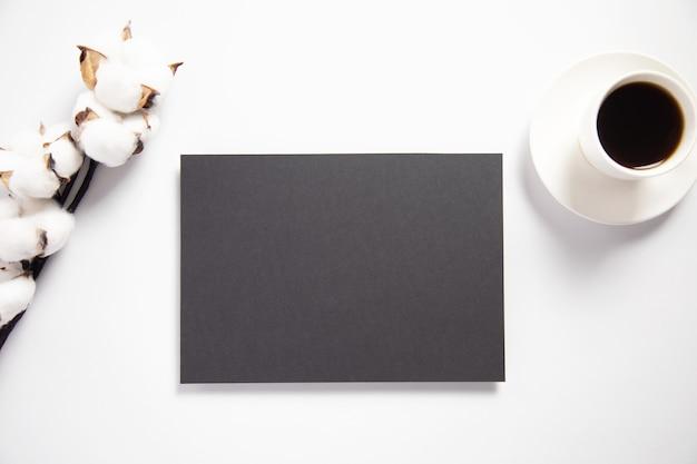 Maquete de cartão preto com um galho de algodão e café