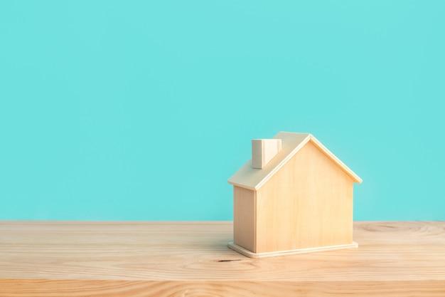 Maquete de casa feita de madeira com cor pastel azul no fundo da mesa de madeira
