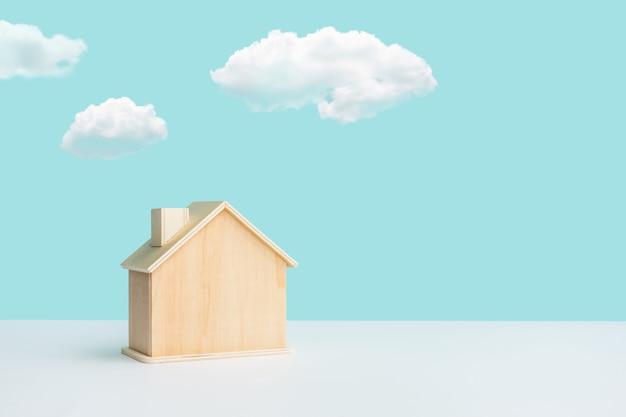 Maquete de casa feita em madeira com céu sobre fundo cor pastel