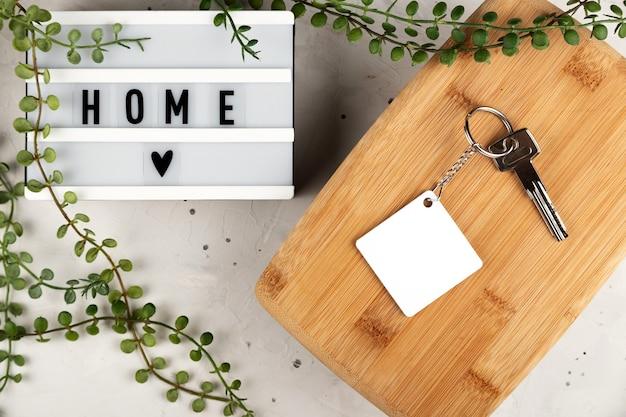 Maquete de chaveiro de sublimação de losango em branco ao lado do quadro com maquete de chaveiro de inscrição em casa ...