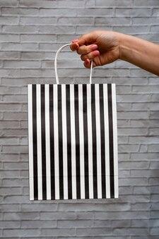 Maquete de close-up de embalagem ecológica em um fundo cinza de tijolo. bolsa kraft em listras pretas e brancas na mão de uma mulher. compras online