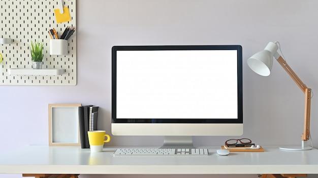 Maquete de computador de espaço de trabalho e material de escritório com placa peg na mesa de madeira.