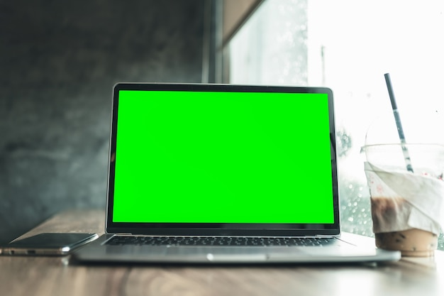 Maquete de computador laptop com tela vazia com café e smartphone isolado na mesa de escritório de madeira na cafeteria como o plano de fundo, tela verde
