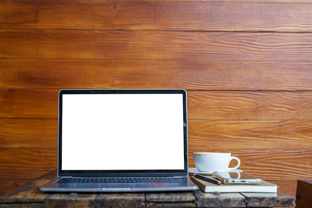 Maquete de computador portátil com tela vazia com notebook, xícara de café e smartphone na mesa do fundo de parede de madeira no café, tela branca