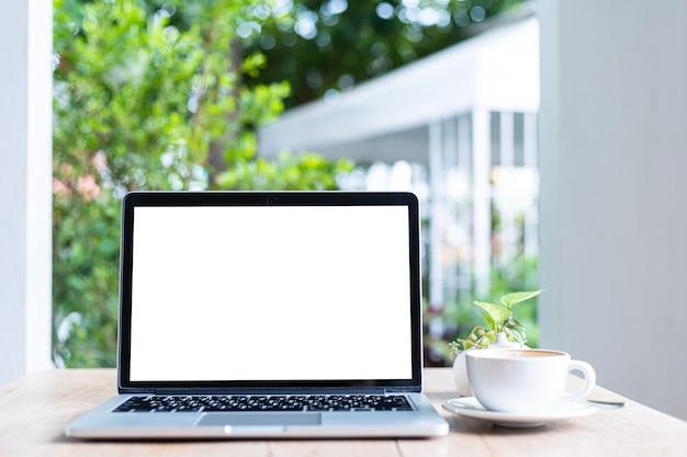 Maquete de computador portátil com tela vazia com xícara de café na mesa do fundo da cafeteria, tela branca