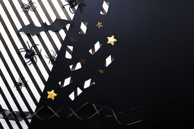 Maquete de convite de festa de halloween, celebração. conceito de decorações de halloween com morcegos, aranhas, jack-o'-lantern, estrelas, confetes, fita. camada plana, vista superior, copie o espaço em fundo preto