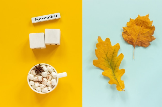 Maquete de cubos em branco e novembro para seus dados de calendário, xícara de cacau e folhas de outono amarelas