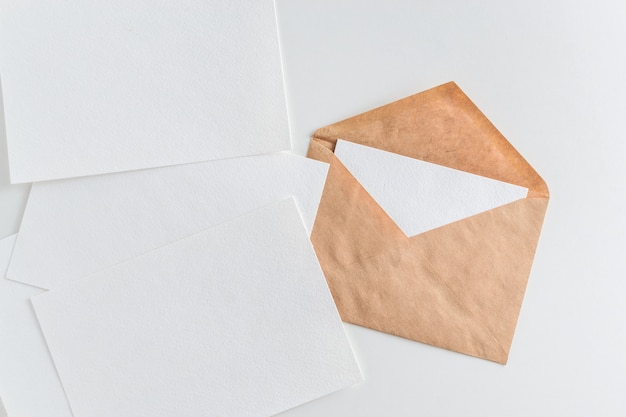 Maquete de envelope e papel branco em branco sobre fundo branco