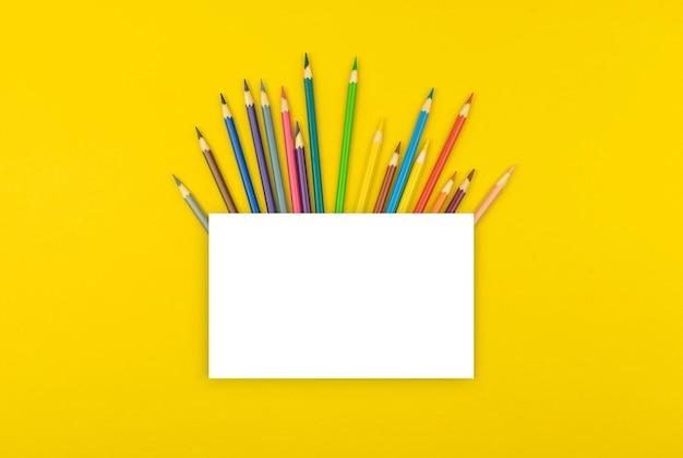 Maquete de escola criativa com papel branco em branco e lápis de cor na área de trabalho, fundo amarelo, espaço de cópia e foto de vista superior
