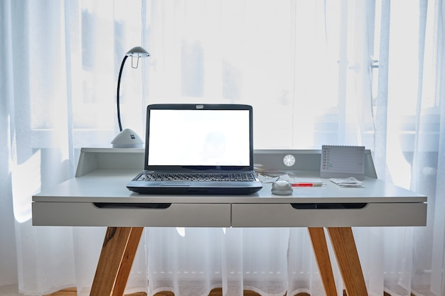 Maquete de escritório em casa. computador portátil em uma sala iluminada, trabalhando em casa e o conceito de quarentena.